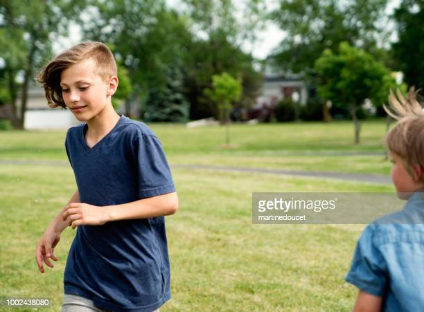 """young boys running and playing in suburb park. - """"martine doucet"""" or martinedoucet foto e immagini stock"""