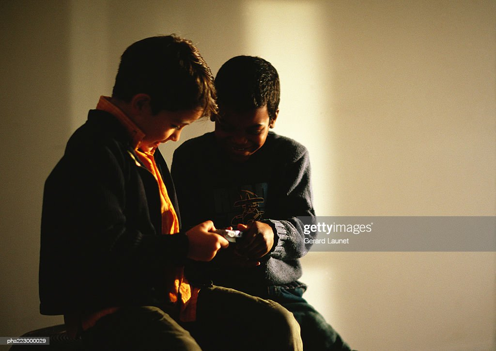 Young boys sitting and looking at game. : Stockfoto