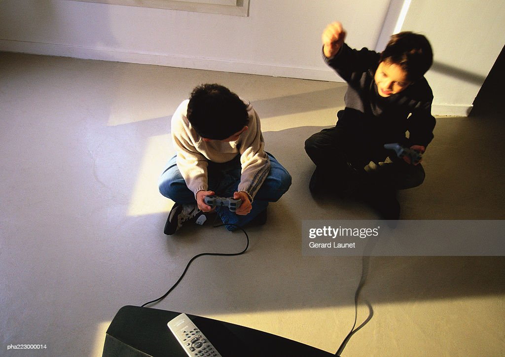 Young boys sitting on floor playing video game. : Stockfoto