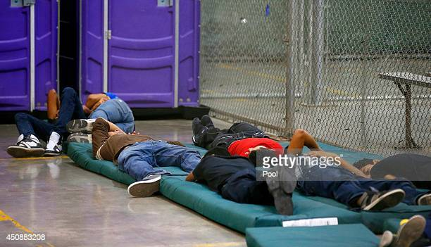 Young boys sleep in a holding cell where hundreds of mostly Central American immigrant children are being processed and held at the US Customs and...