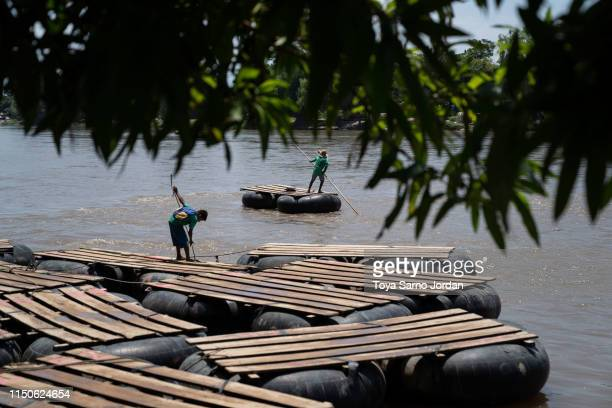 Young boys stand on rafts on June 18 2019 on the Suchiate River in Ciudad Hidalgo in Chiapas Mexico The Mexican government launched a deployment of...