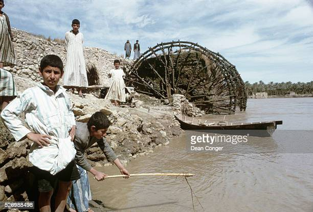 Young boys stand on the banks of the Euphrates River near an ancient water wheel Hit Iraq