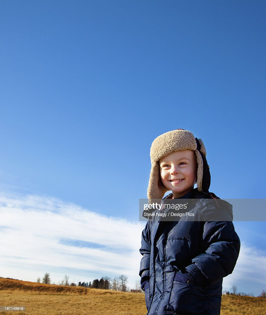 A Young Boys Stands On A Grass Field Wearing A Coat And Hat : Stock Photo