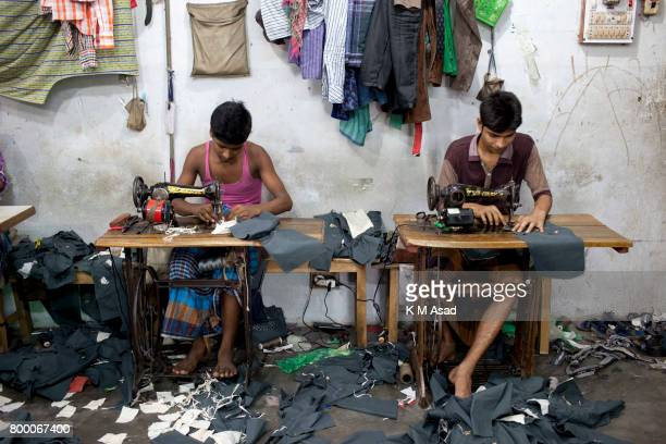 SADARGHAT DHAKA BANGLADESH Young boys stitch a cloth in a local garment shop in Dhaka Bangladesh World Day Against Child Labor was observed on 12...