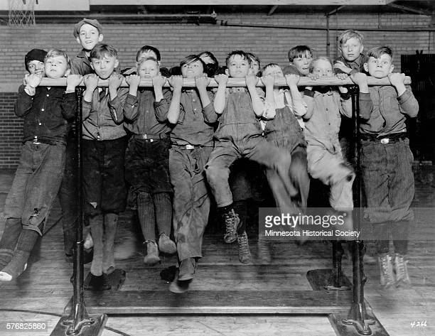 Young boys struggle to lift their chins over the chinup bar at the Pillsbury Settlement House Minneapolis Minnesota ca 1926