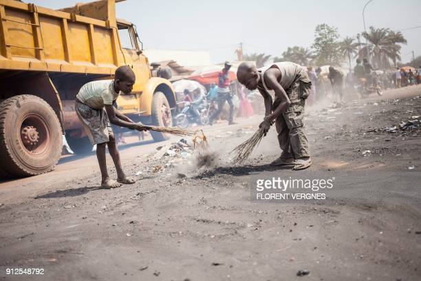 TOPSHOT Young boys sweep rubble in the street near a market after a blaze which damaged 47 shops on January 17 in Bangui's predominantly Muslim PK5...