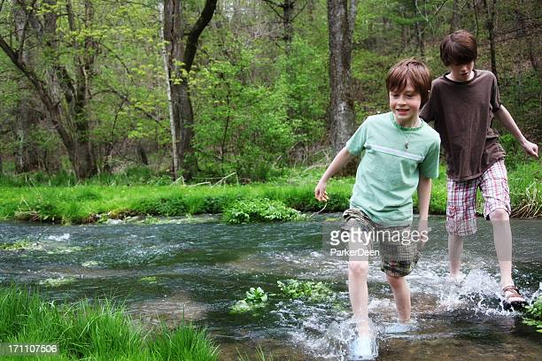 Young boys wading through a stream flowing across a forest