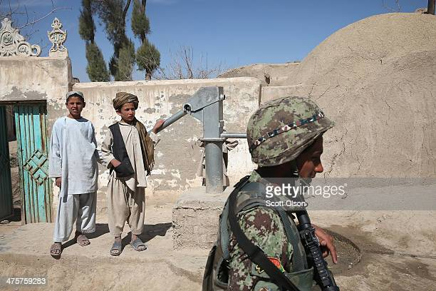 Young boys watch as a soldier from the Afghan National Army walks through a village during a joint patrol with the US Army's 4th squadron 2d Cavalry...
