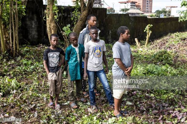 Young boys watch as the famous Bambeto Cemetery is cleaned in Conakry on September 18 as the Bambeto cemetery is where most opposition supporters who...