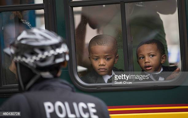 Young boys watch from a seat in a charter bus as demonstrators march along Michigan Avenue to protest police abuse December 13 2014 in Chicago...