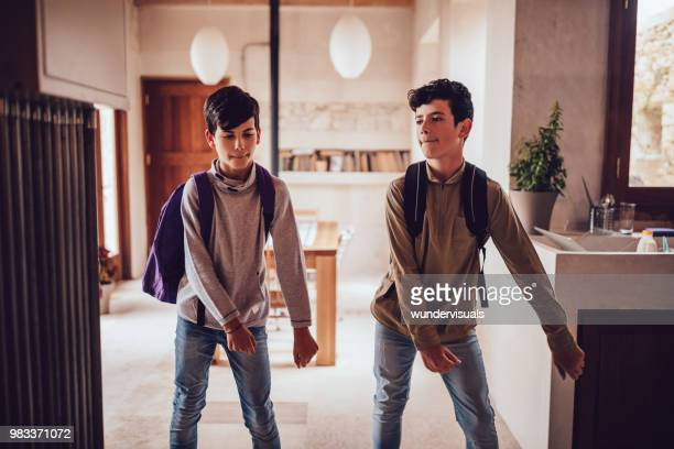 young boys with backpacks doing the floss dance at home - boys stock pictures, royalty-free photos & images