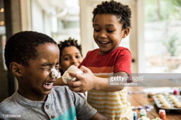 young boys with cake frosting on faces at party - naughty america stock pictures, royalty-free photos & images