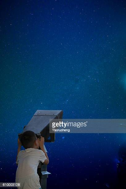 Young boys with telescope at open window looking at night sky