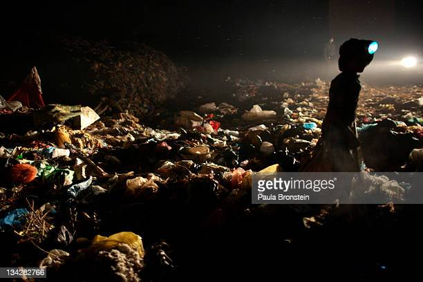 Young boys work late into the night recycling garbage at the local garbage dump November 30 2011 in Siem Reap Cambodia Many children work part time...