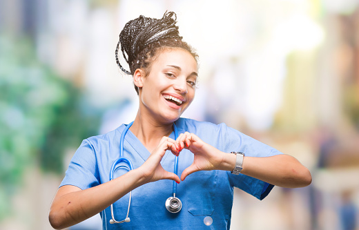 Young braided hair african american girl professional surgeon over isolated background smiling in love showing heart symbol and shape with hands. Romantic concept. 1069301576