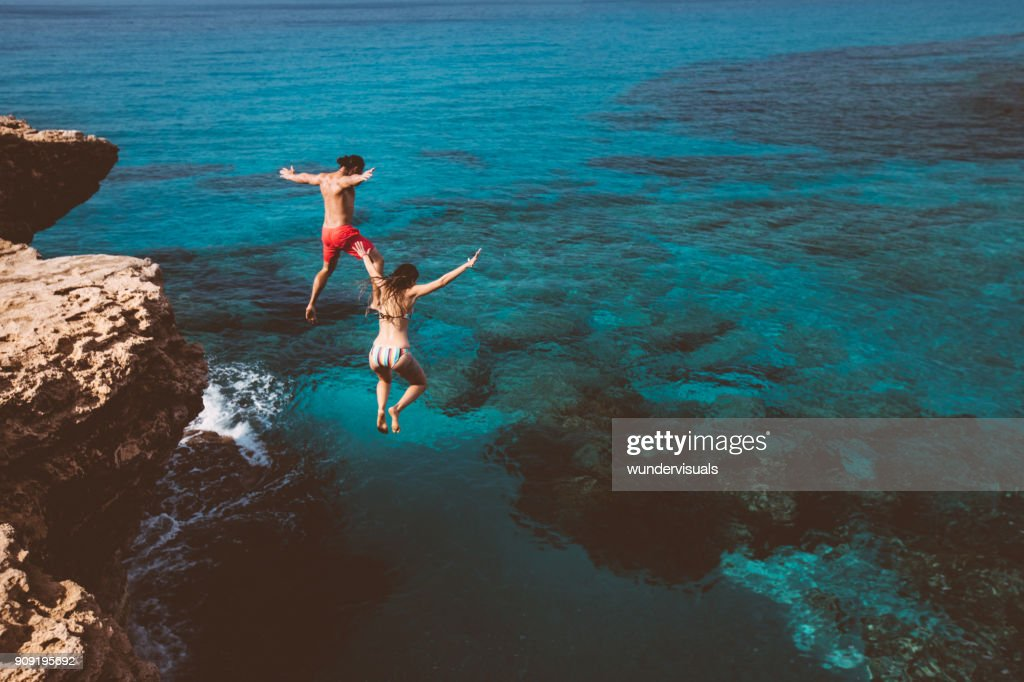 Young brave divers couple jumping off cliff into ocean : Stock Photo