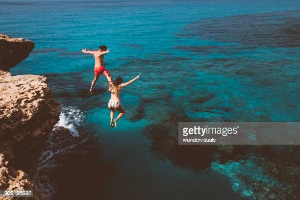 Young brave divers couple jumping off cliff into ocean
