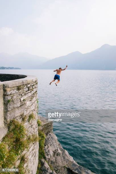 Young brave man diving in the water from a cliff.