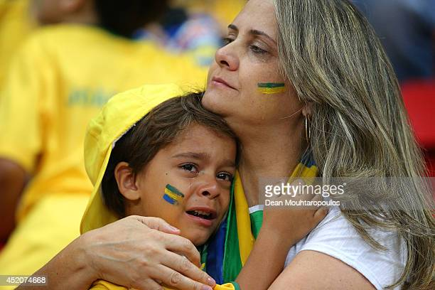 A young Brazil fan is consoled after being defeated by the Netherlands 30 during the 2014 FIFA World Cup Brazil Third Place Playoff match between...