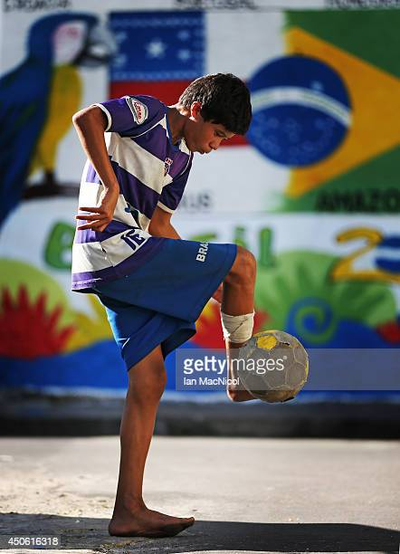 A young Brazilian boy plays football in the street prior to the opening Group D match of the 2014 World Cup between England and Italy at Arena...