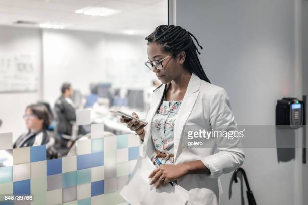 young brazilian businesswoman looking at mobile in office