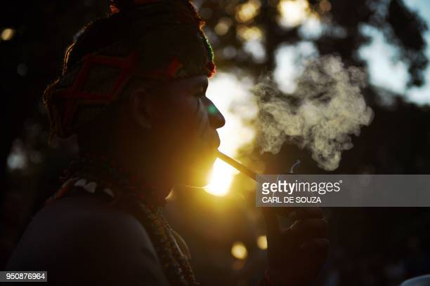 A young Brazilian indigenous man is pictured as he smokes at the Acampamento Terra Livre in Brasilia on April 24 2018 Approximately 2500 indigenous...