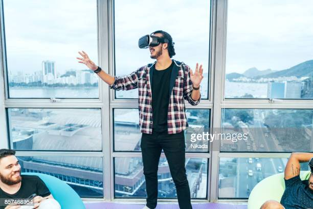 Young brazilian man using the virtual reality headset