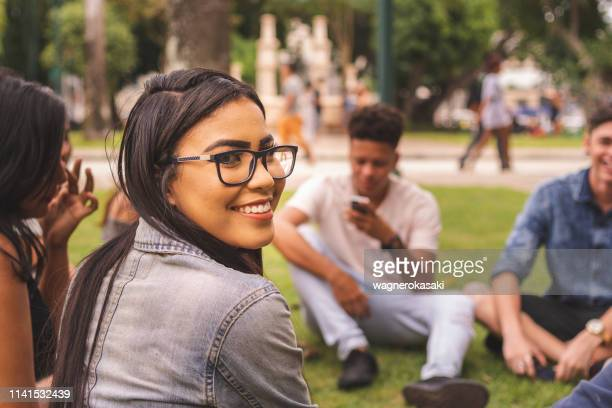 young brazilian woman enjoying time with her friends at a public park - university student stock pictures, royalty-free photos & images