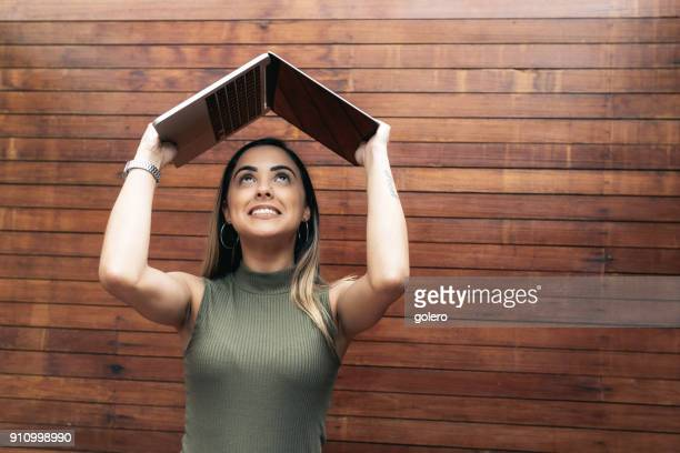 young brazilian woman holding laptop over head