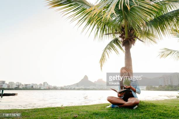 young brazilian woman reading a book outdoors at rio de janeiro - coconut water stock pictures, royalty-free photos & images