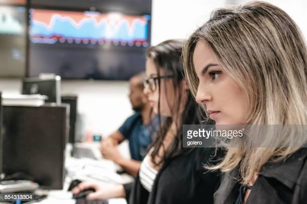 大きなオフィス内のコンピューターで働く若いブラジル人女性
