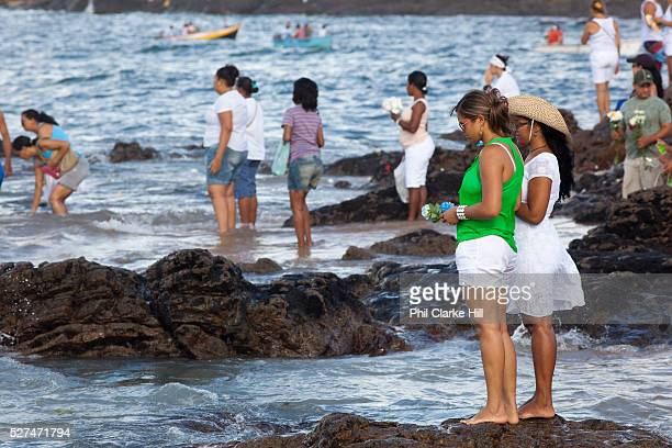 Young Brazilian women making offerings of flowers to the sea in honour of Yemanja February 2nd is the feast of Yemanja a Candomble Umbanda religious...