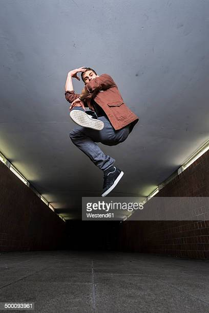 Young breakdancer jumping in the air in underpass