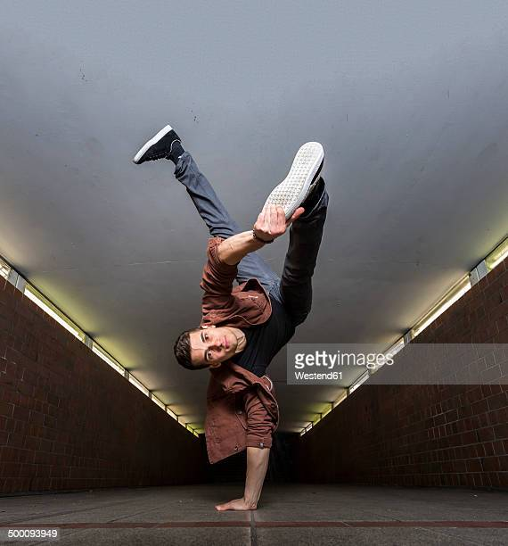 young breakdancer performing a handstand in underpass - breakdancing stock photos and pictures