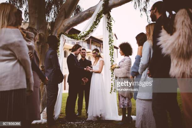 young bride and groom getting married and exchanging rings outdoors - wedding vows stock pictures, royalty-free photos & images