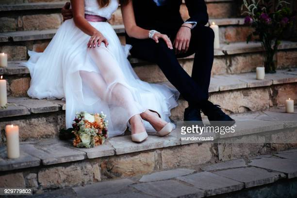 young bride and groom relaxing together on stone steps - marito foto e immagini stock