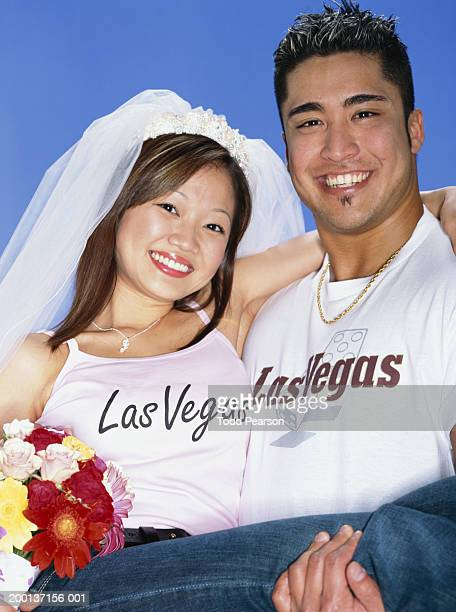 Young bride and groom wearing 'Las Vegas' T-shirts, portrait
