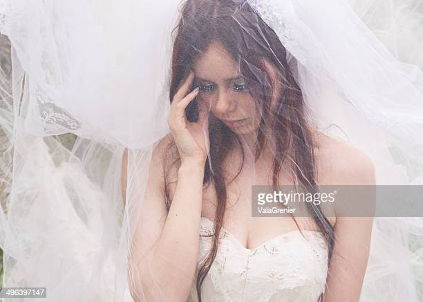 young bride behind layer of tulle touching face. - bride stock pictures, royalty-free photos & images