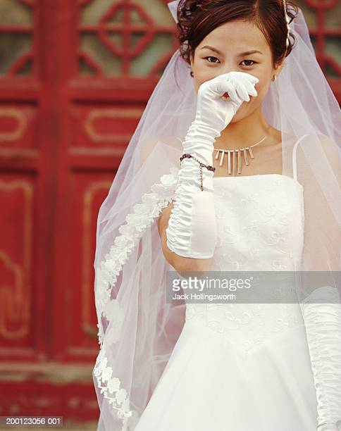 Young bride covering smile with hand, portrait