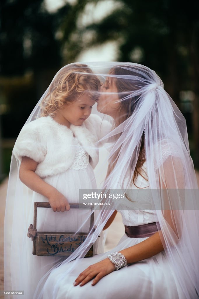 Young bride embracing and kissing little flower girl at wedding : Stock Photo