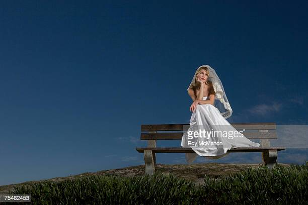 young bride sitting on bench resting chin on hand - veil stock photos and pictures