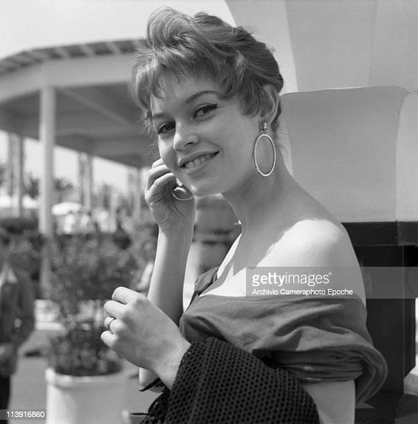 A young Brigitte Bardot french model singer and actress at Cannnes Movie Festival wearing a nudeback shirt and big round earrings Cannes 1955