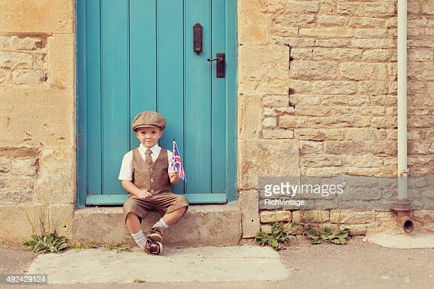 Young British Boy Sits on Doorstep With Union Jack