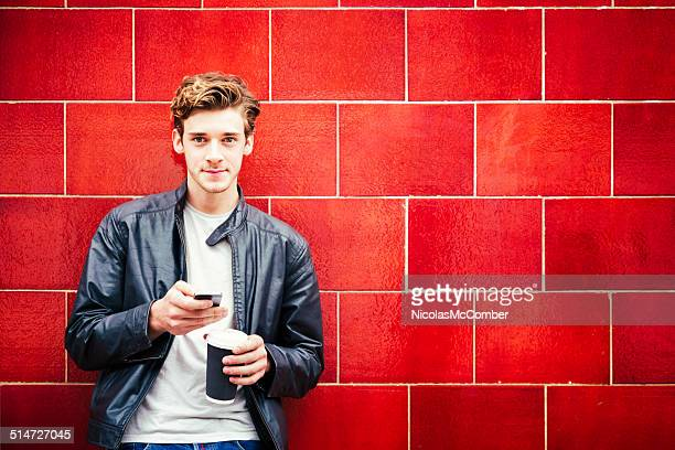 Young British man portrait against red wall