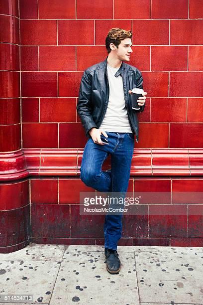 Young British Mann warten auf den bus