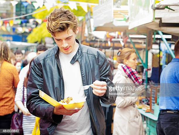 Young British man walking in market eating street food