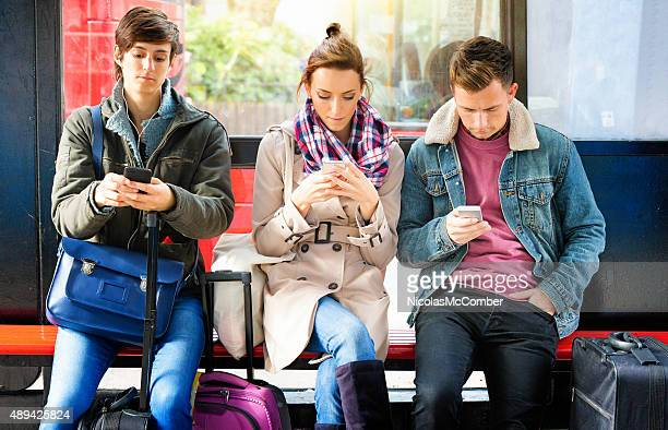 Young British people waiting for bus obsessed with mobile phones