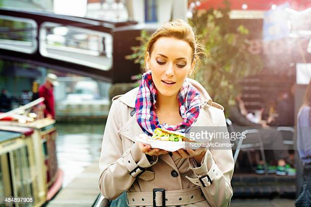 young british woman looks at take-out food with appetite - onderweg stockfoto's en -beelden