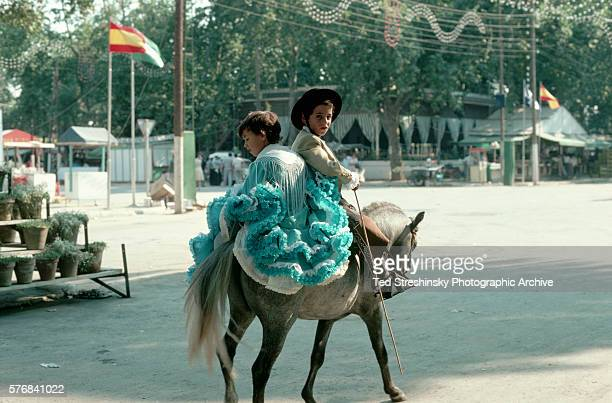 Young brother and sister, dressed in traditional Andalusian costumes, ride through a park on a pony on their way to the annual sherry grape harvest...
