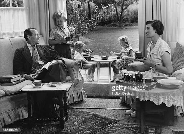 A young brother and sister eat afternoon tea on a patio while the rest of their family relax inside